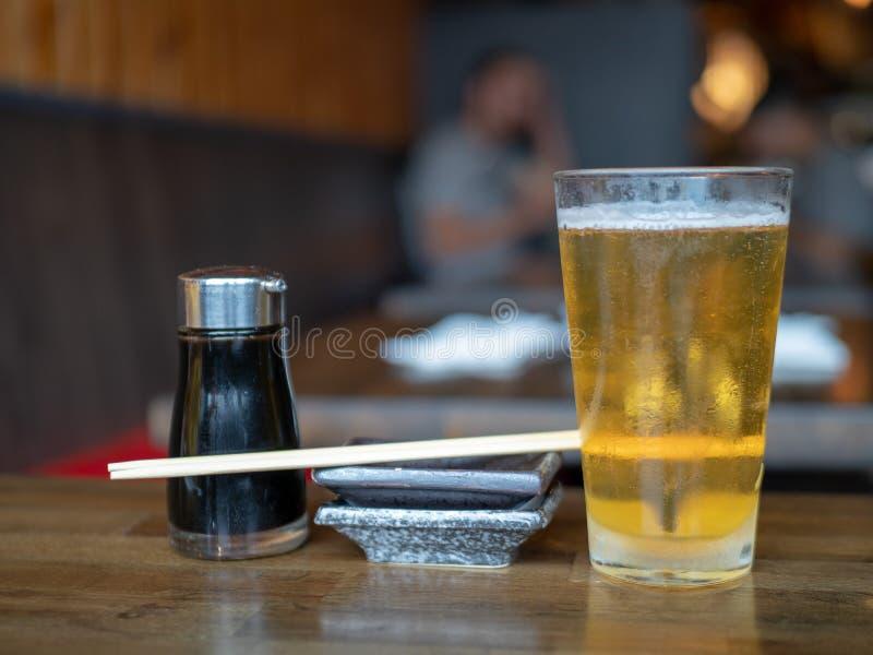 Erogatore della salsa di soia, piatto, bastoncini di legno e vetro della pinta riempito di birra sulla tavola immagini stock libere da diritti