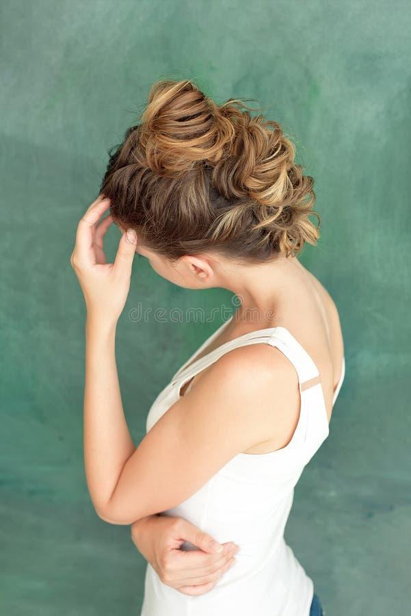 时尚一个美丽的深色的夫人的演播室画象有一种别致的发型的在一件白色女衬衫的erokez样式 免版税图库摄影