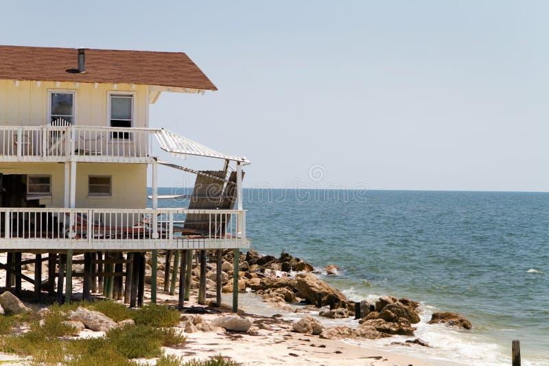 Erosão de praia da casa imagem de stock