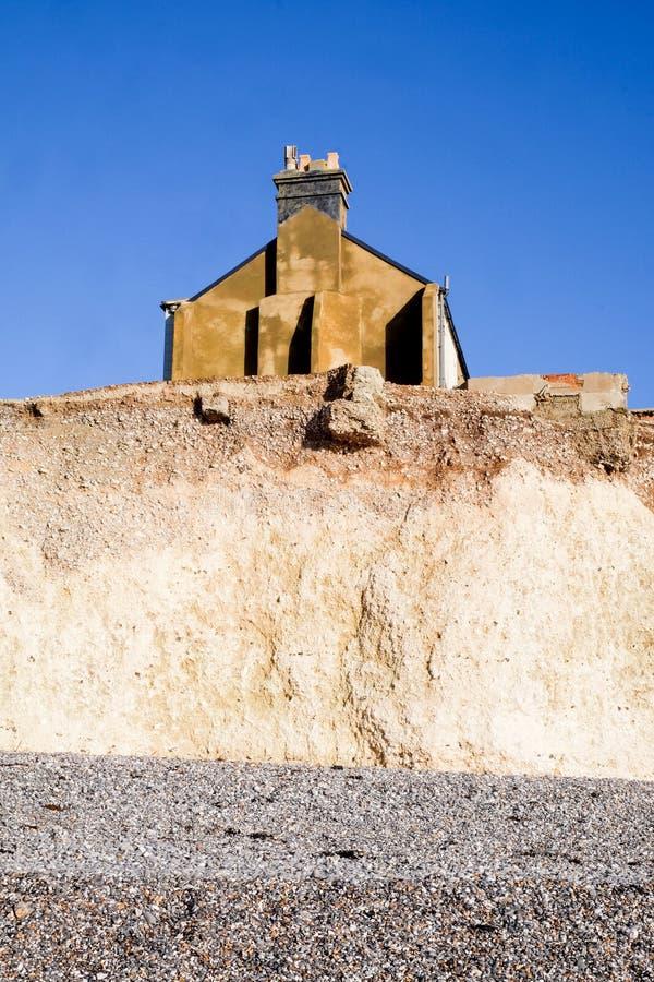 Erosión, lado de una casa colgante que se sienta en el borde de un cha blanco imagen de archivo