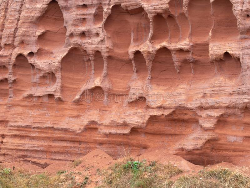 Erosion in the red sandstone coastal cliffs at Budleigh Salterton, Devon, UK. Geology on the Jurassic coast. stock images