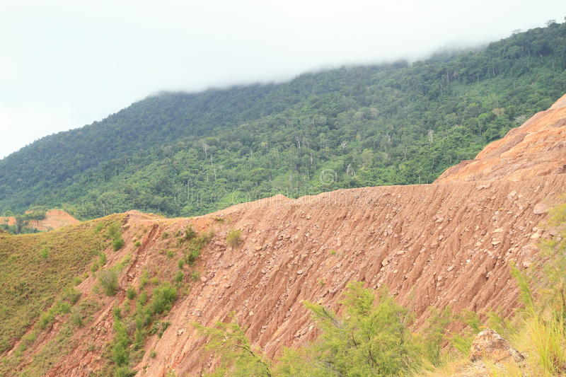 Erosion. Of soil on stone slope of hill on green mountain with top hidden in clouds - geological minerals stock photo