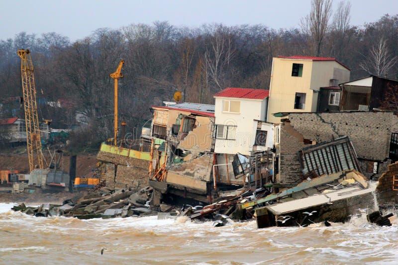 Erosione costiera - le case costruite sul terreno argilloso debole fanno scorrere giù al mare fotografia stock libera da diritti
