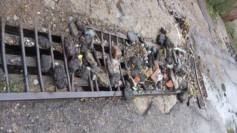 Erosione idrica del fondo della strada Foro del pericolo, contesto grigio di pietra Asfalto rotto Flusso ostruito dei detriti, la immagini stock