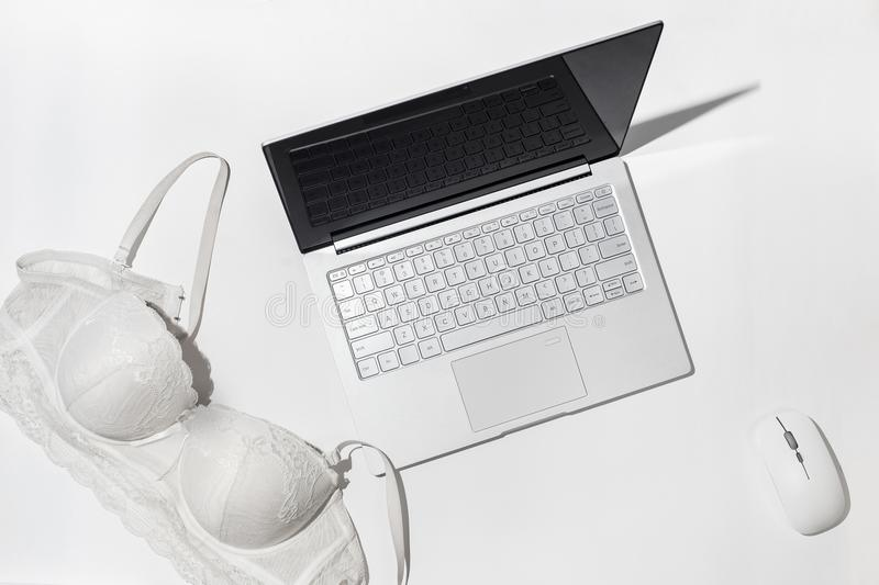 Erotic chat, virtual sex concept. White bra thrown on a modern laptop, against a white background. Minimalistic Flat lay. Top view royalty free stock photography