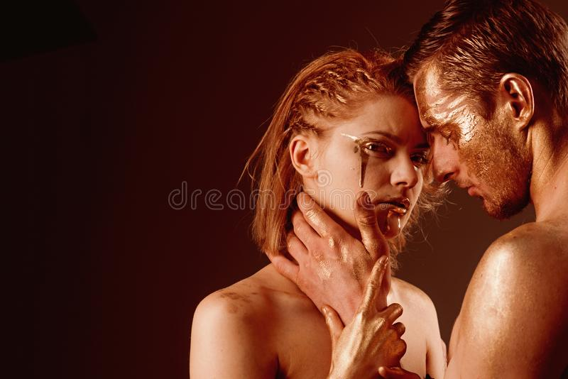 Erotic games of couple in love. Sexy couple with golden body art makeup, copy space. Gold spa and skincare treatment. Golden collagen mask and beauty. 24K Gold royalty free stock photo
