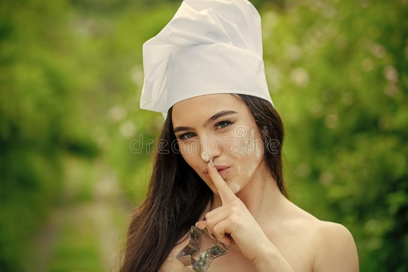 Erotic housewife. Girl in chef hat making hush gesture. Woman with finger on lips on natural background. Secret and silence concept royalty free stock image
