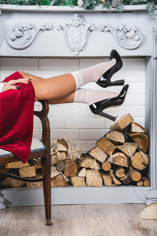 Erotic legs in white socks and black shoes. Young female legs on a christmas decorated wall background stock photo