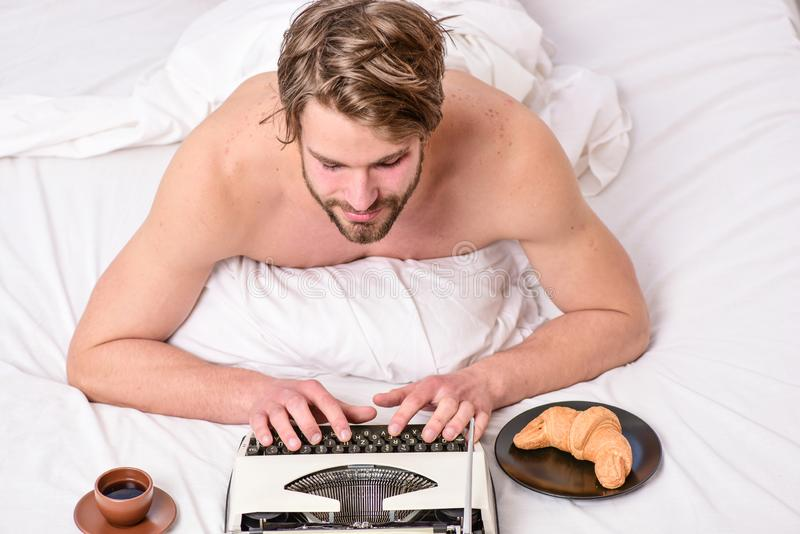 Erotic literature. Daily routine of writer. Writer handsome author used old fashioned manual typewriter. Man writer lay. Bed with breakfast working. Morning royalty free stock images
