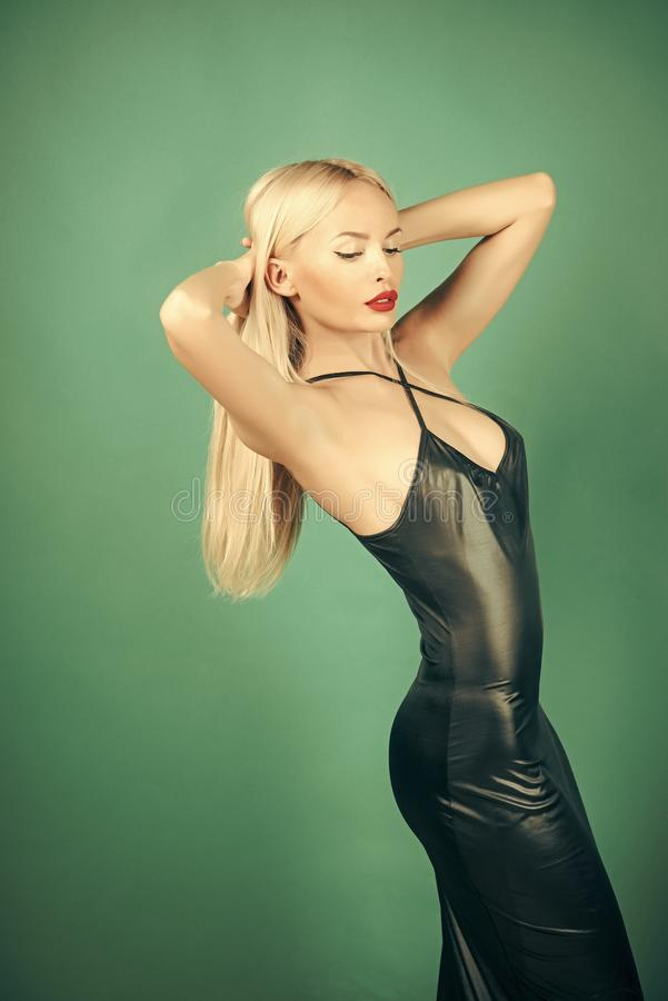 Erotic and seduction. Woman posing in black latex dress. Fashion and beauty. Girl with long blond hair on green background. Glamour lifestyle concept royalty free stock photography
