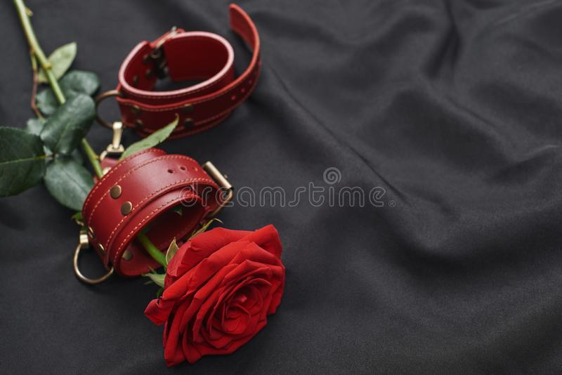 Erotic toys. Top view of red leather handcuffs and rose against of black silk fabric. Human sexuality concept royalty free stock images