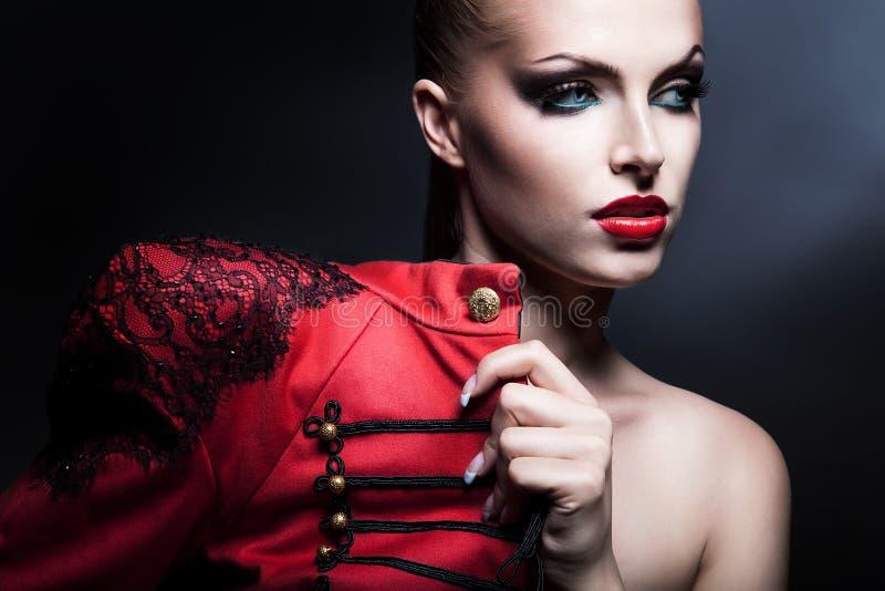 Erotische attraktive Frau im Rot mit blauen Augen stockbild