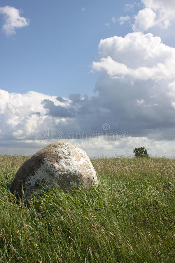 Erratic boulder. Frog perspective ao an erratic boulder against a bright blue sky with friendly clouds royalty free stock image