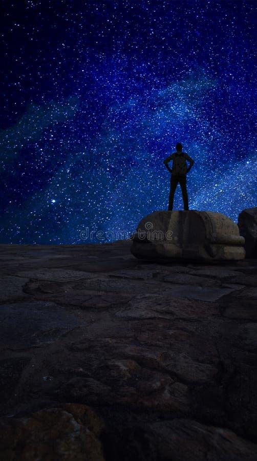 Erreichen Sie für den Stern-Mann, der auf Rock gegen Galaxie sternenklares s steht stockfotos