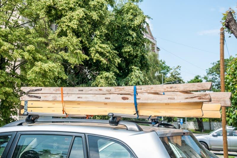 Errichtende Leitern des hölzernen Werkzeugs gebunden am Dachgepäckträger des Autos für Innenerneuerung des Hauses stockbild
