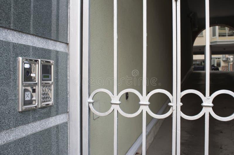 Errichtet in die Wandwechselsprechanlage mit einem Tor und einer Aussicht des Hofes im Hintergrund mit dem Bogen stockfotografie