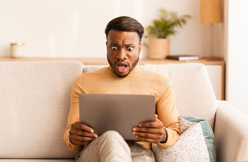 Shocked Man Looking At Laptop Screen Sitting On Sofa At Home royalty free stock image