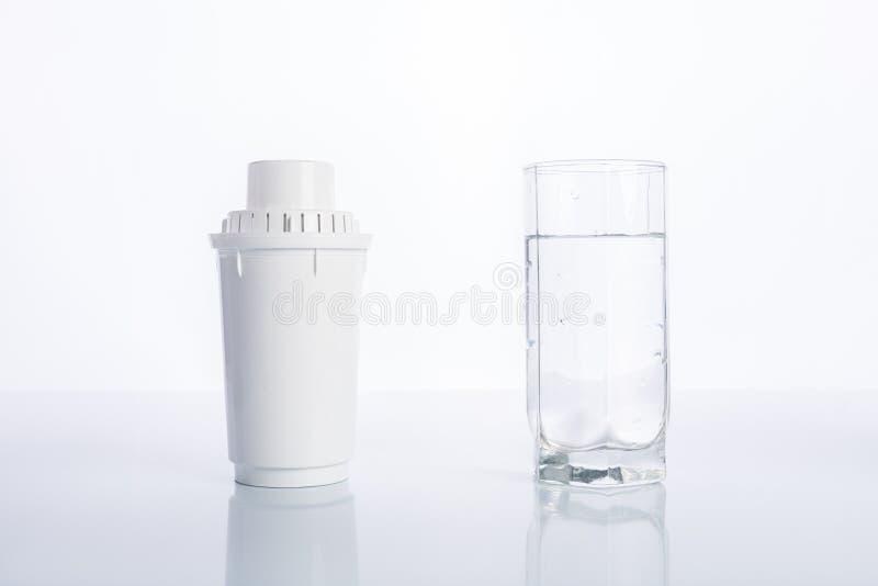Ersatzwasserfilter und Glas gereinigtes Wasser auf weißem Hintergrund, Reflexion lizenzfreies stockfoto