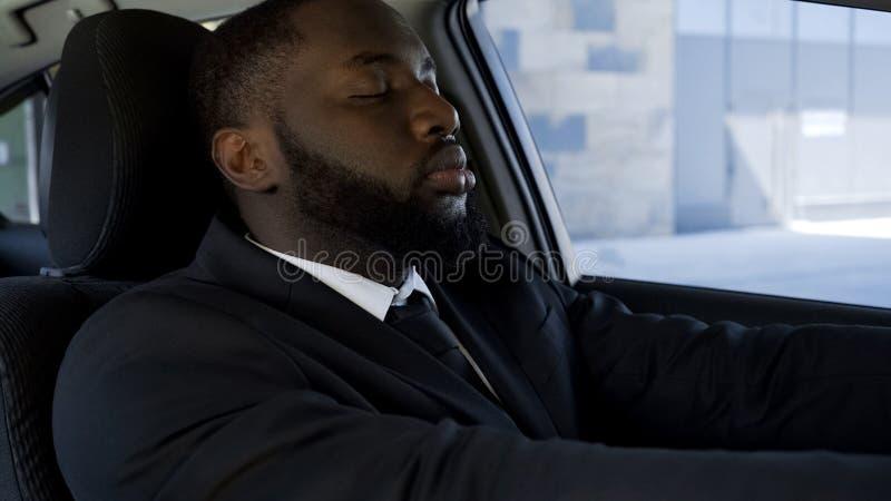 Erschöpft von der aktiven Lebensart den schwarzen Mann, der in Auto, ermüdet von der Arbeit einschläft lizenzfreies stockbild