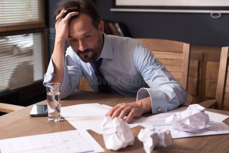 Erschöpfte Arbeitsüberstunden des freudlosen Mannes lizenzfreie stockfotografie