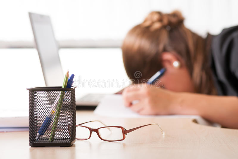 Erschöpfte Frau, die bei der Arbeit schläft stockfotografie