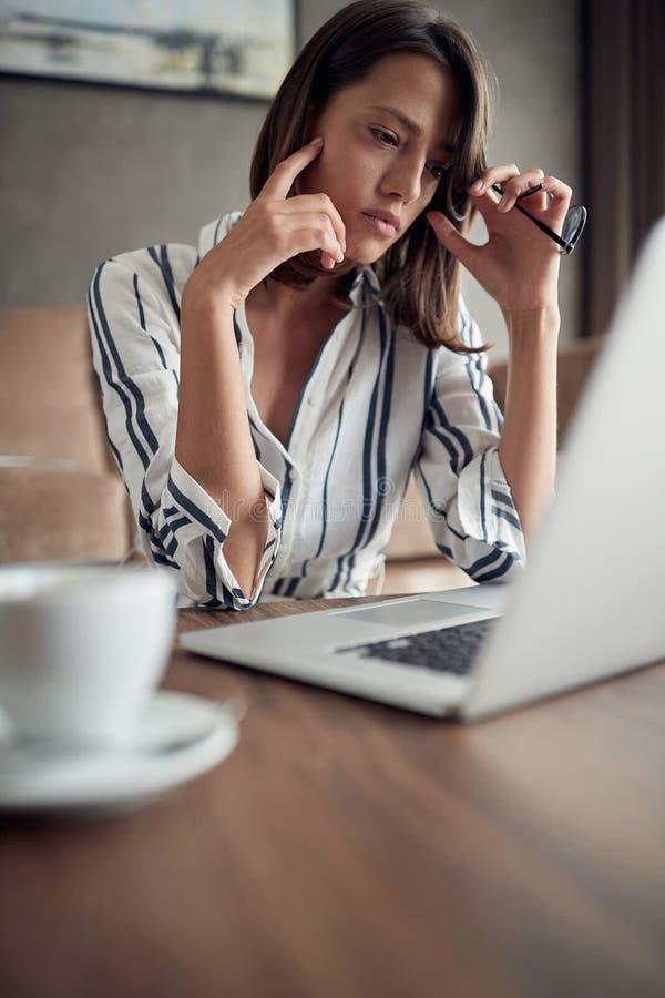 Erschöpfte Geschäftsfrau, die zu Hause mit einem Laptop als freies arbeitet stockfoto