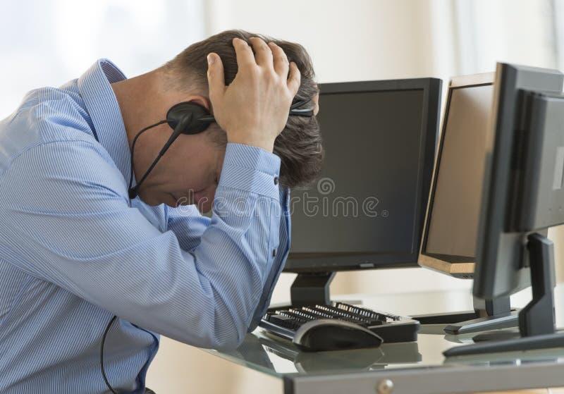Erschöpfte Händler-With Head In-Hände, die am Computertisch sich lehnen stockfotos