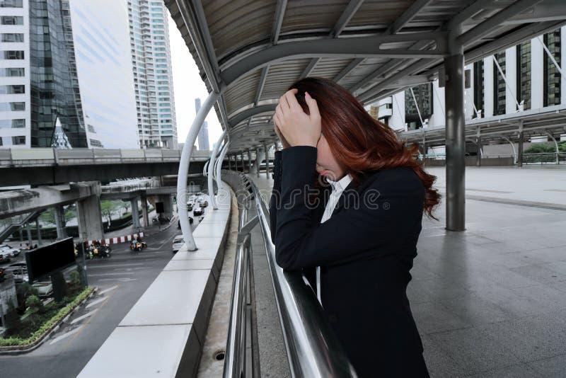 Erschöpfte junge asiatische Geschäftsfrau mit der Hand auf Gesichtsgefühl ermüdete und Burnout mit seiner Arbeit am Stadthintergr lizenzfreie stockbilder