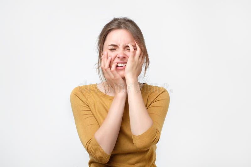 Erschöpfte junge Frau in der gelben Strickjacke, die ihren Kopf mit Augen berührt, schloss stockfoto