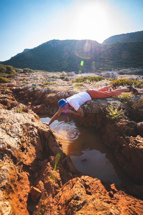 Erschöpfter Abenteurer trinkt Wasser von einem Spalt in einem Felsen stockfotos