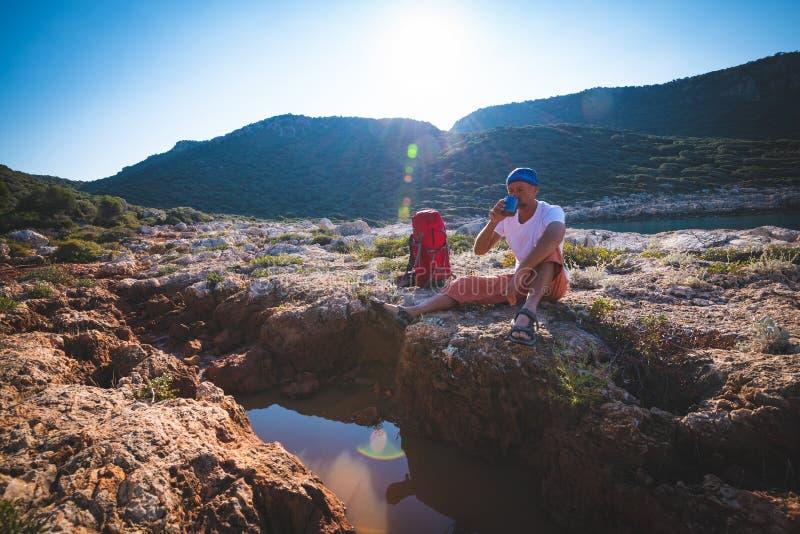 Erschöpfter Abenteurer trinkt Wasser von einem Spalt in einem Felsen stockfotografie
