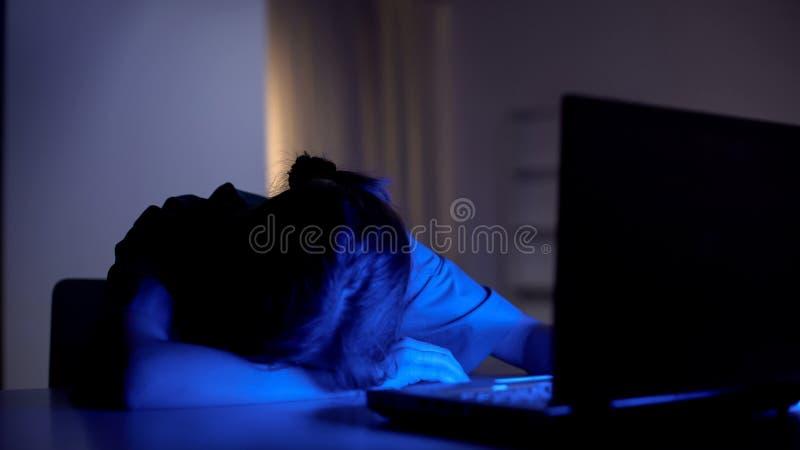 Erschöpfter Doktor, der im vorderen Arbeitslaptop, ermüdende Nachtschicht in der Klinik schläft lizenzfreie stockfotografie