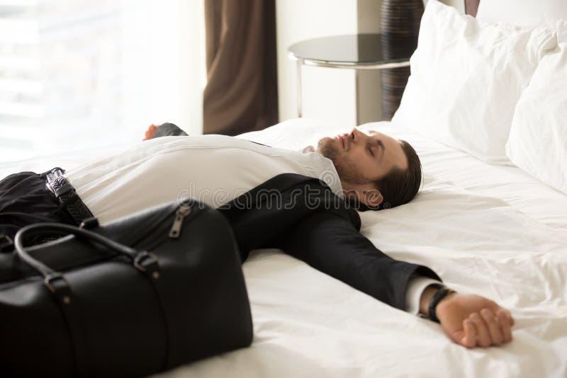 Erschöpfter Geschäftsmann, der auf Bett im Hotelzimmer legt lizenzfreies stockbild
