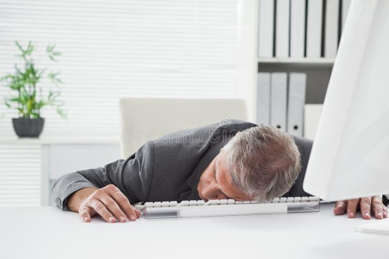 Erschöpfter Geschäftsmann, der an seinem Schreibtisch schläft stockbild