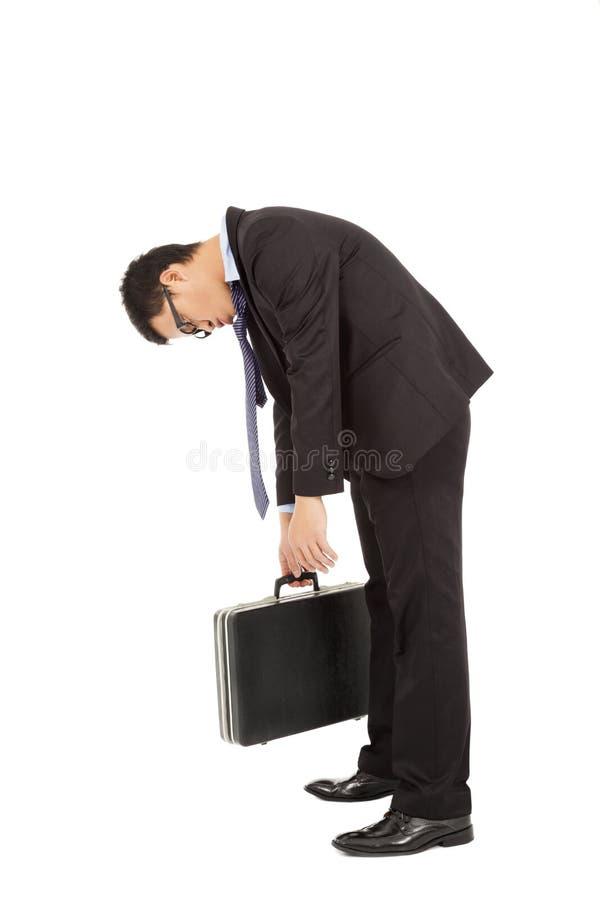 Erschöpfter Geschäftsmannkrummer rücken und halten Aktenkoffer stockfotos