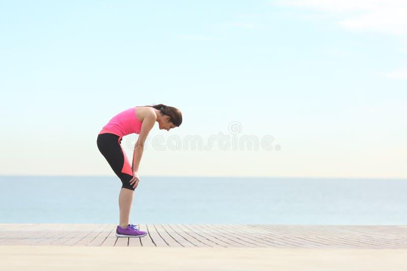 Erschöpfter Läufer, der auf dem Strand nach Übung stillsteht lizenzfreies stockfoto