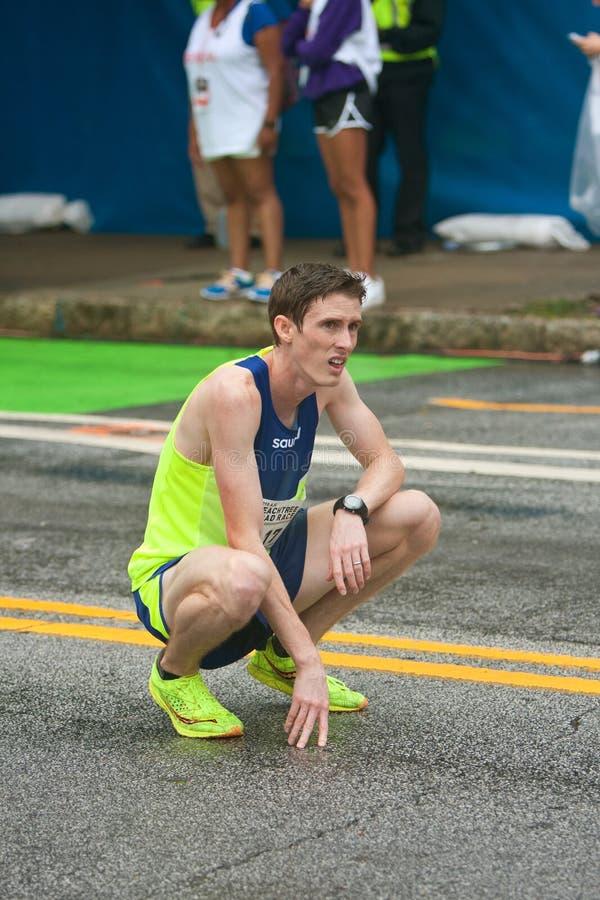 Erschöpfter Läufer knit, um Atem an Peachtree-Straßenrennen zu fangen stockbild