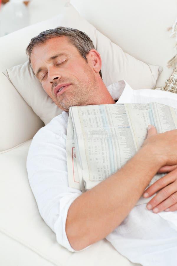 Erschöpfter Mann, der auf der Couch schläft stockfotografie