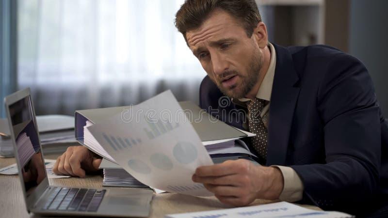 Erschöpfter Mann umgeben durch Schreibarbeit im Büro, das Diagramme, Frist betrachtet lizenzfreies stockfoto