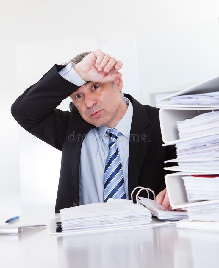 Erschöpfter reifer Geschäftsmann At Work stockbild