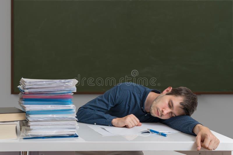 Erschöpfter und überarbeiteter Lehrer schläft auf Schreibtisch im Klassenzimmer stockfoto