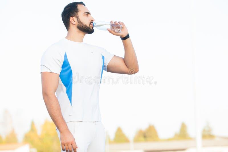 Erschöpftes Läufermann-Getränkwasser auf dem Park nach Training stockbild