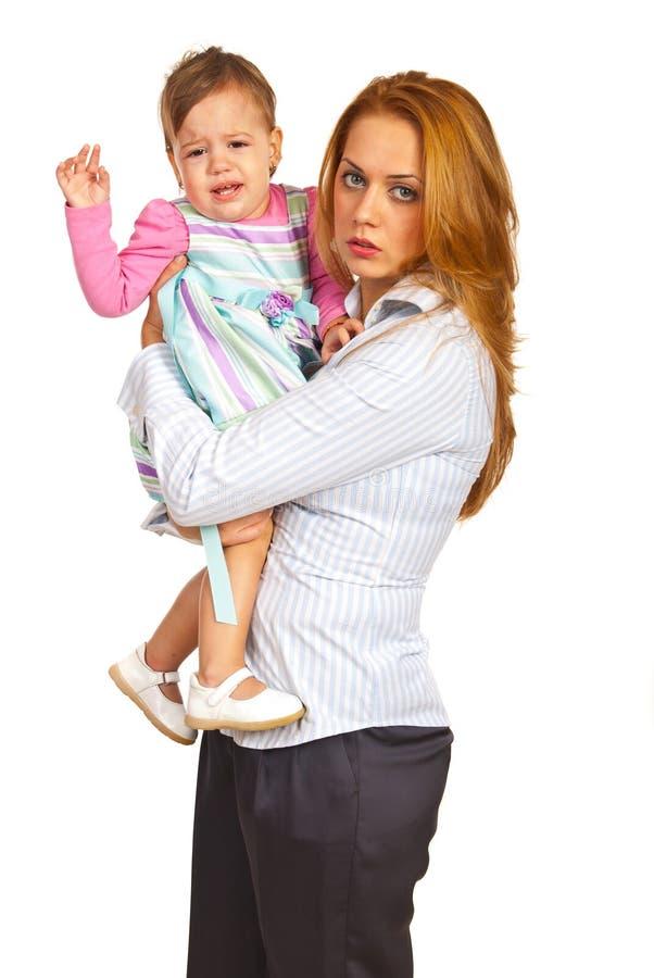 Erschöpftes Mutter- und Schreienmädchen stockfoto