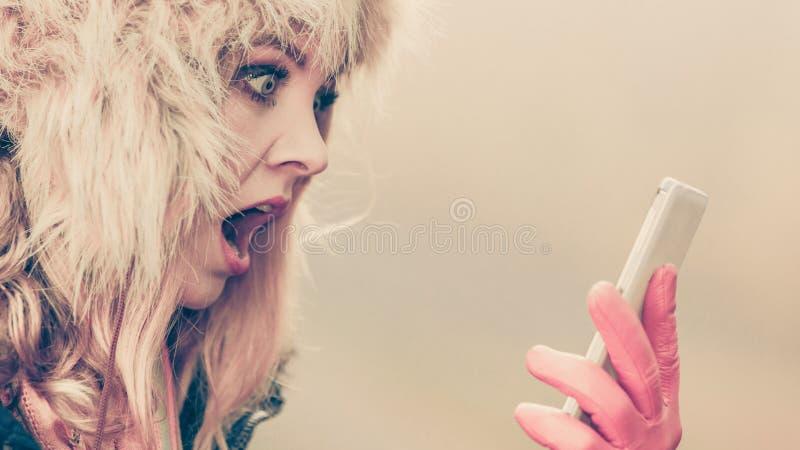 Erschrockene ängstlichfrau, die am Handy spricht stockbild