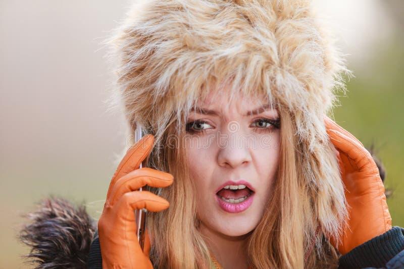 Erschrockene ängstlichfrau, die am Handy spricht stockfotografie