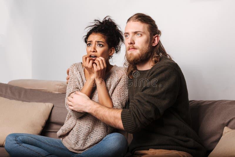 Erschrockene Dame, die frightenedly Horrorfilm während ihr Mann nahe sitzt und umarmt sie aufpasst stockbild