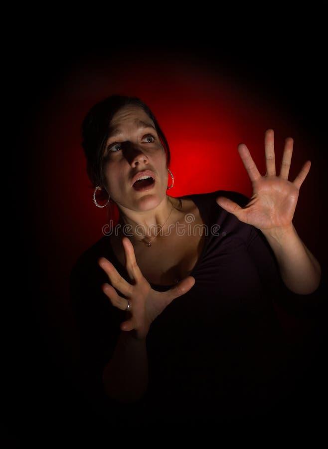 Erschrockene Frau auf dunklem Hintergrund lizenzfreie stockfotos