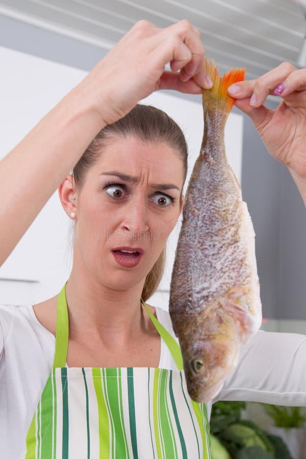 Erschrockene Frau, die Fische in der Küche kocht stockbilder
