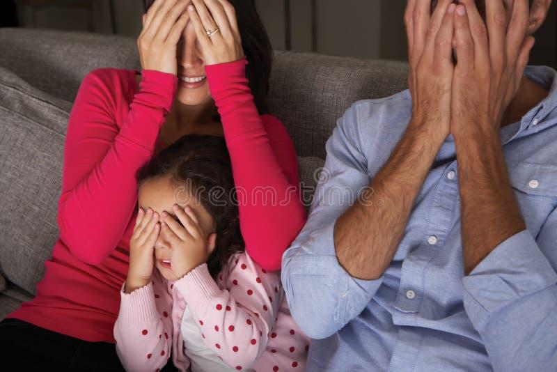 Erschrockene hispanische Familie, die im Sofa And Watching Fernsehen sitzt stockfotos