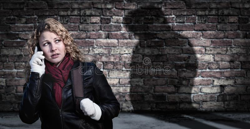 Erschrockene junge erwachsene Frau benutzt Handy als mysteriöse männliche Schatten-Zahl lauert in der Nähe stockfotografie